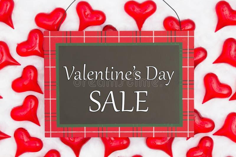 Alla hjärtans dag Sale-meddelande om hängskylt med röda hjärtan på vit väv royaltyfria bilder