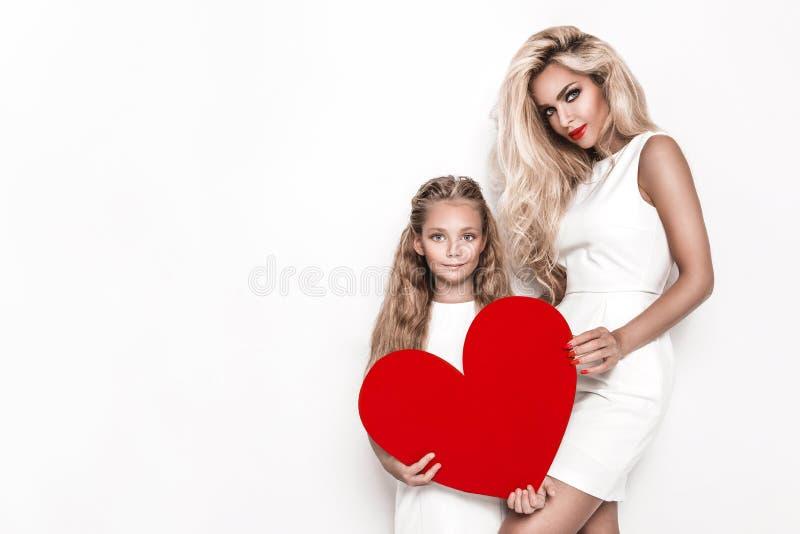 Alla hjärtans skönhets-flickors mor och dotter på vit bakgrund Vackra, glada unga kvinnor, mamma och dotter på Alla hjärtans dag arkivfoton