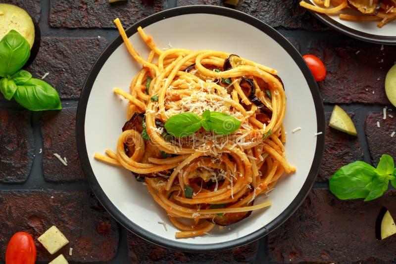 Alla italiano vegetariano Norma degli spaghetti della pasta con melanzana, i pomodori, il basilico ed il parmigiano immagini stock