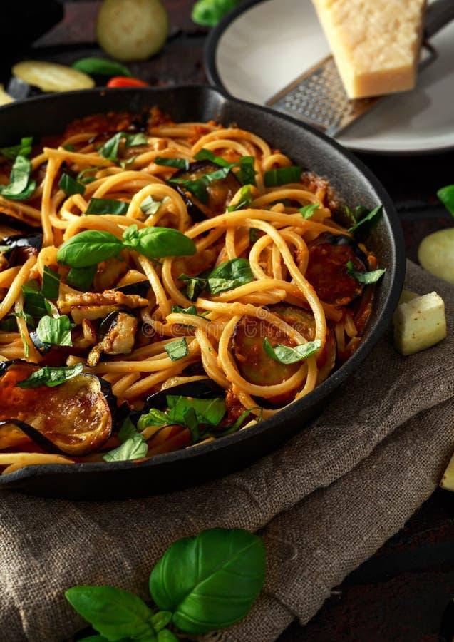 Alla italiano vegetariano Norma degli spaghetti della pasta con melanzana, i pomodori, il basilico ed il parmigiano in pentola ru fotografia stock libera da diritti