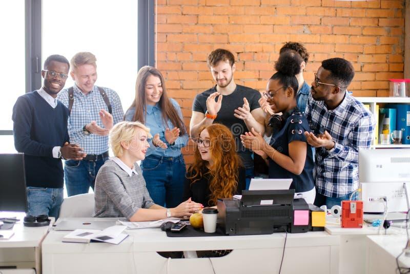 Alla medlemmar av företaget som gör en komplimang till deras partner med rött långt hår som bär den svarta blusen royaltyfri foto