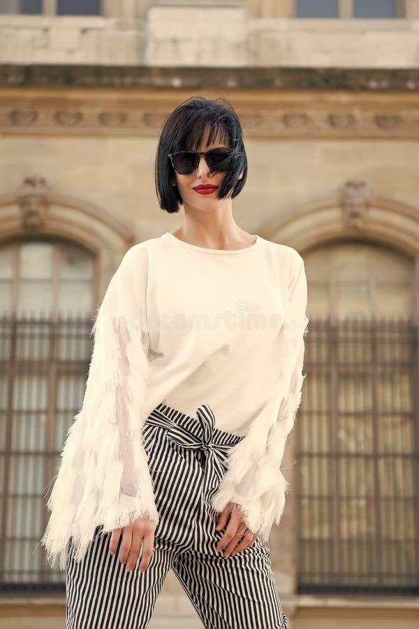 Alla moda e comodo Posa alla moda del modello della donna all'aperto L'acconciatura castana del peso della ragazza sembra alla mo fotografia stock