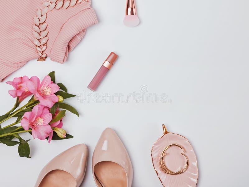 Alla moda impallidisca accessori e fiori femminili rosa immagini stock
