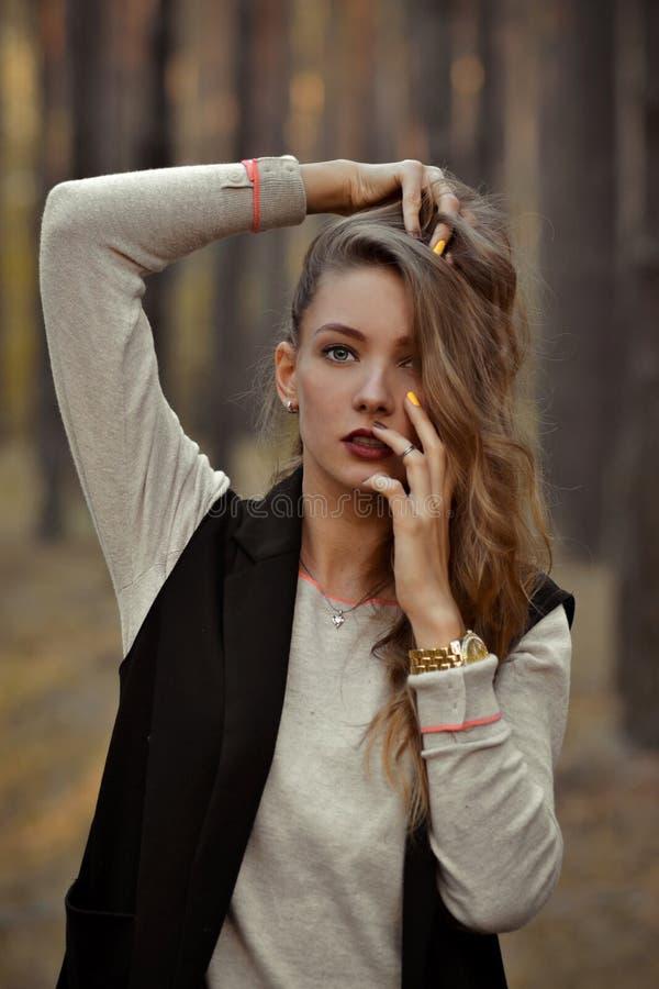 Alla moda, posando ragazza con le dita e le mani eleganti vicino al fronte Femmina sveglia e bella all'aperto in foresta con il f immagine stock