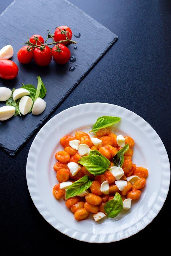 Alla Sorrentina van aardappelgnocchi in tomatensaus met groene verse basilicum en mozarellaballen diende op een plaat royalty-vrije stock foto's
