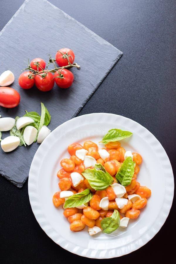 Alla Sorrentina van aardappelgnocchi in tomatensaus met groene verse basilicum en mozarellaballen diende op een plaat stock foto