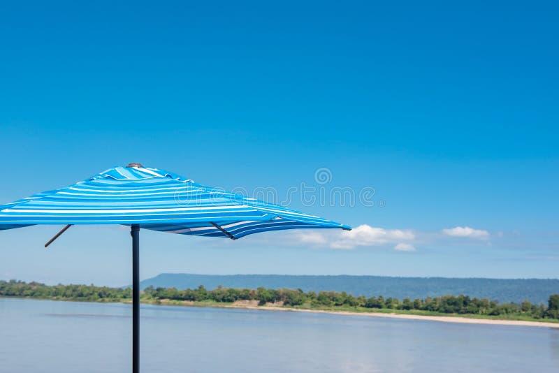 Alla vista del fiume in cielo blu calmo di estate, vento, sole ed ombrello variopinto immagini stock libere da diritti