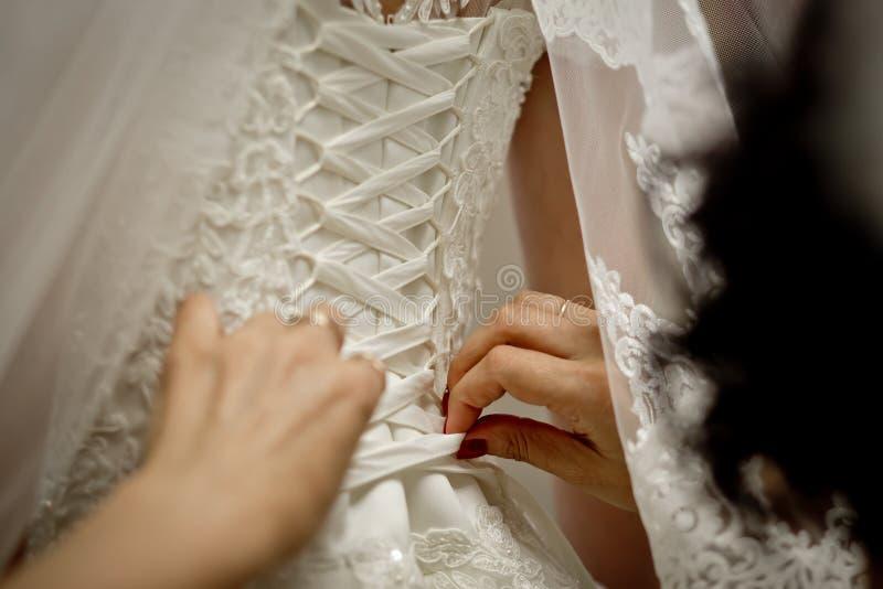 Allacciamento di un vestito da sposa della sposa fotografia stock libera da diritti