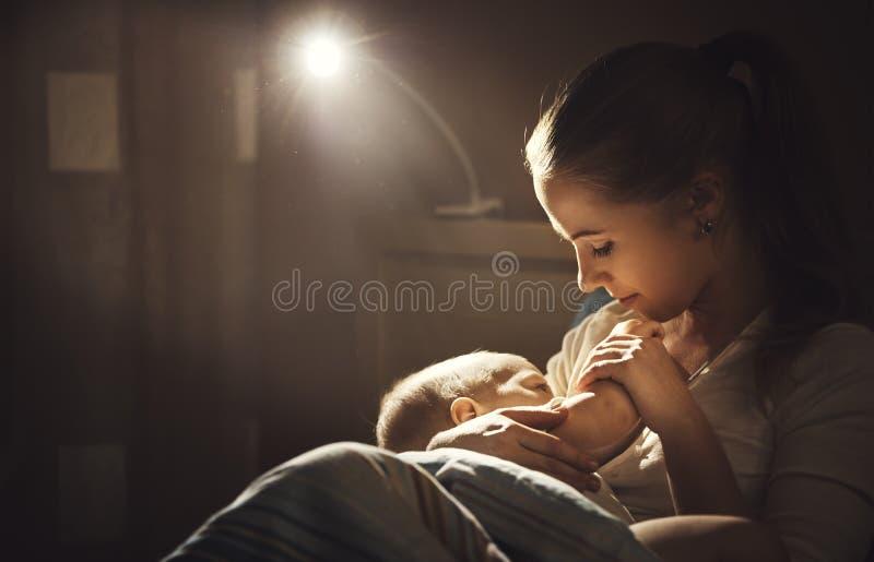 Allaitement enfantez le sein de alimentation de bébé dans la nuit d'obscurité de lit images stock