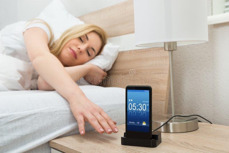 Allarme sonnecchiante della donna sullo schermo del telefono cellulare fotografie stock libere da diritti