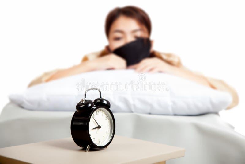 Allarmklok met slaperig Aziatisch meisje stock foto
