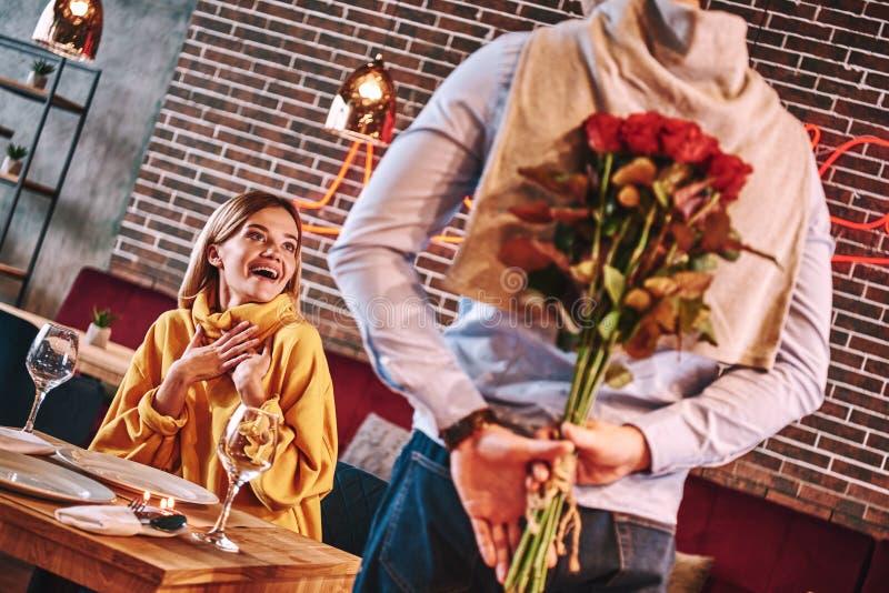 Alle beste voor vrouw De mens in blauw overhemd verraste zijn mooi blondemeisje stock foto