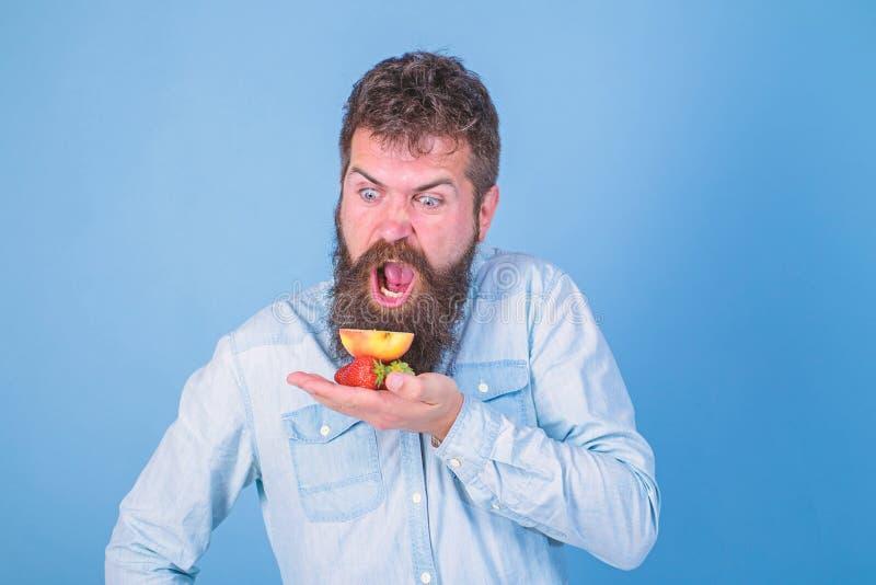 Alle f?r mich Schreiendes hungriges Gesicht des Mannes mit Bart isst organische Festlichkeiten B?rtige Grifferdbeeren und -apfel  lizenzfreies stockfoto