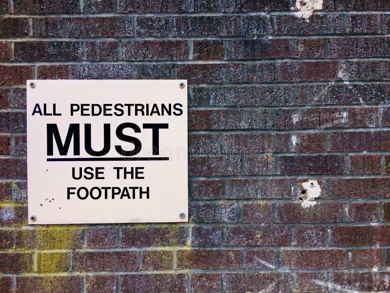 Alle Fußgänger müssen den Fußweg benutzen stockbild