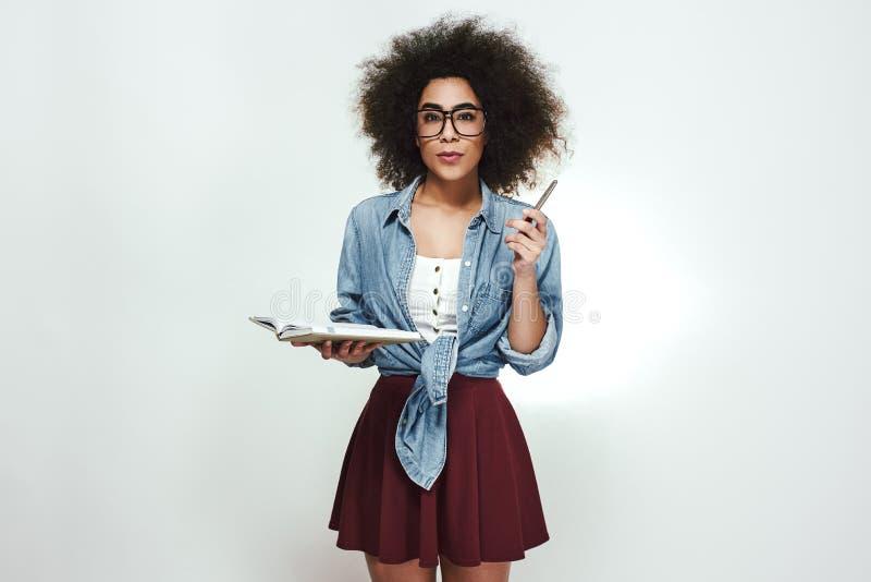Alle Ideen müssen geschrieben werden Überzeugte junge afrikanische Frau im Eyewear, der ihr Notizbuch und Stift hält und Kamera b stockbild