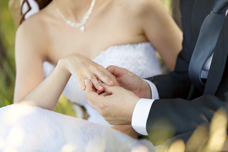Alle nozze, lo sposo mette l'anello sul dito della sposa fotografia stock libera da diritti