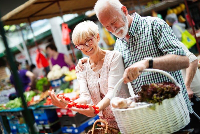 Alleen de beste groenten en fruit Schitterend volwassen koppel dat vers voedsel op de markt koopt stock afbeelding