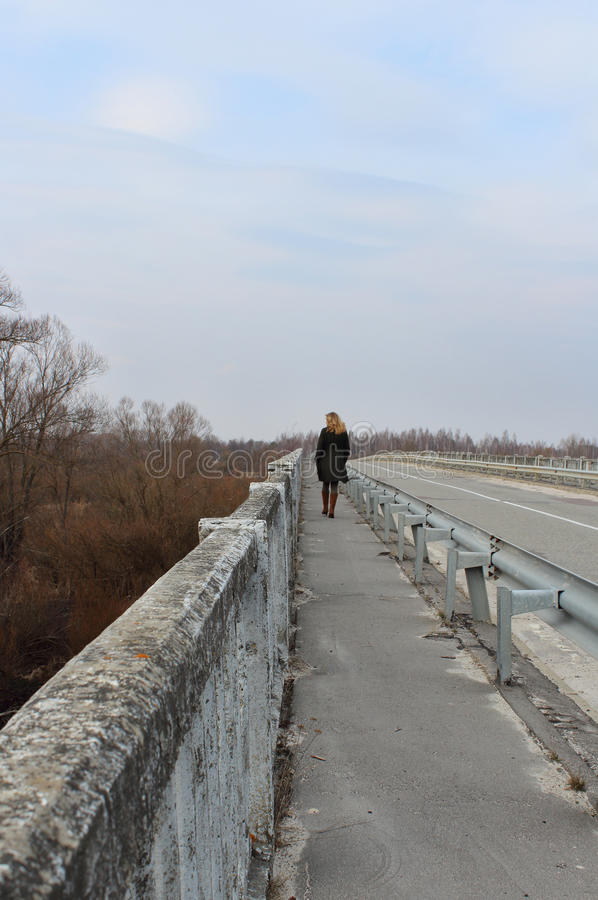 Alleen meisje in een zwarte laag op de oude brug - Achtermening stock fotografie