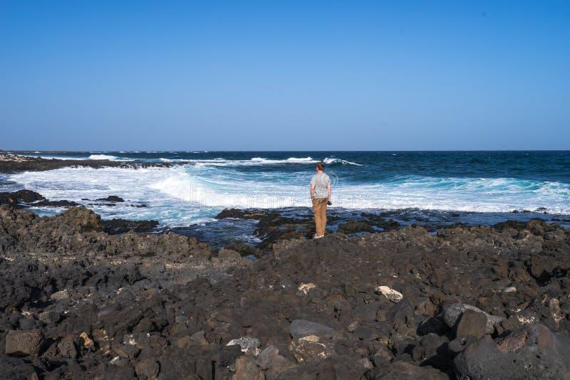 Alleen mens op de rotsachtige kustlijn van de Atlantische Oceaan royalty-vrije stock afbeelding