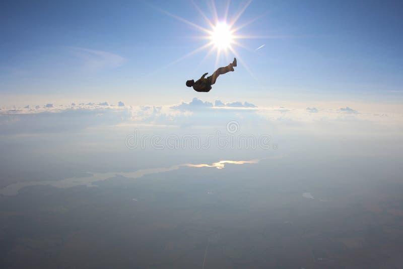 Alleen skydiver valt in de hemel boven horizon stock fotografie