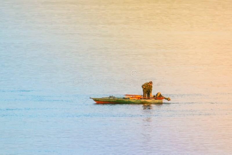 Alleen visser in groene boot Het landschap van het riviermeer eenzaamheid royalty-vrije stock foto's