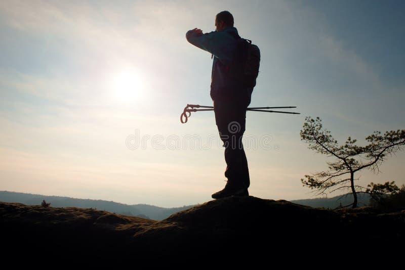 Alleen volwassen mens backpacker bij zonsopgang bij open mening over bergpiek stock afbeeldingen