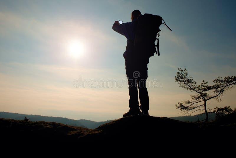 Alleen volwassen mens backpacker bij zonsopgang bij open mening over bergpiek stock foto's