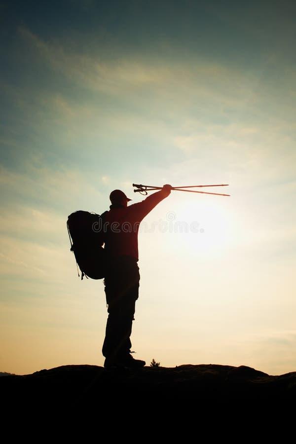 Alleen volwassen mens backpacker bij zonsopgang bij open mening over bergpiek stock foto