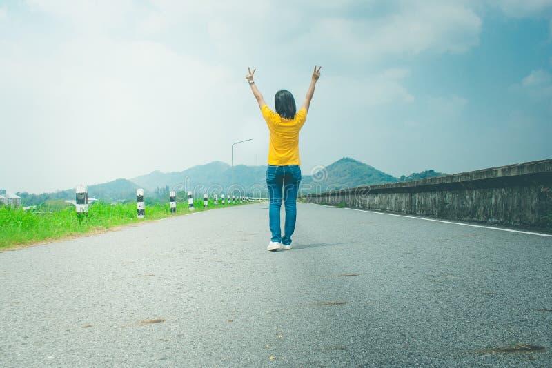 Alleen vrouwenreiziger of backpacker het lopen langs plattelandsweg langs kant met reservoir, boven heft zij handen op stock afbeeldingen