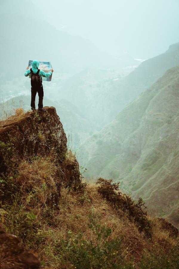 Alleen wandelaar met kaart van het eiland die op een rotsachtige richel voor een schitterende panoramamening blijven van hoge ber stock foto