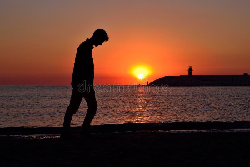 Alleen zich bevindt op de strandjongelui, depressie, vakantie, stock afbeeldingen