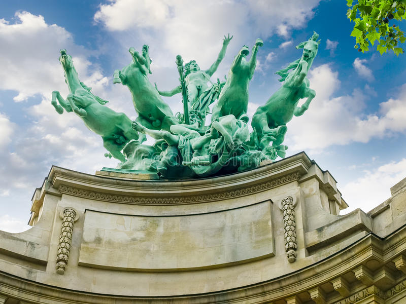 Allegorical statue over facade of Great Palace closeup in Paris royalty free stock images
