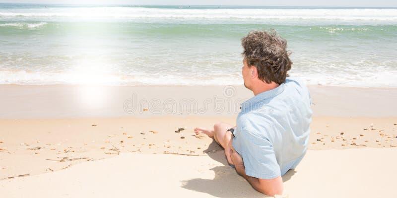 Allein einzelner Mann der hinteren Ansicht, der auf Seeseitensand liegt stockfoto
