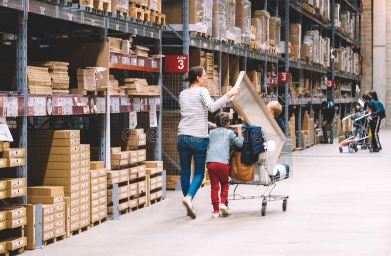 Allein erziehende Mutter-Einkaufen an IKEA-Möbelgeschäft, das Warenkorb drückt lizenzfreie stockfotografie