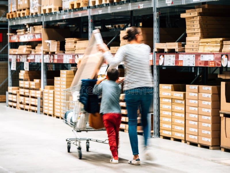 Allein erziehende Mutter-Einkaufen an IKEA-Möbelgeschäft, das Warenkorb drückt stockfotografie