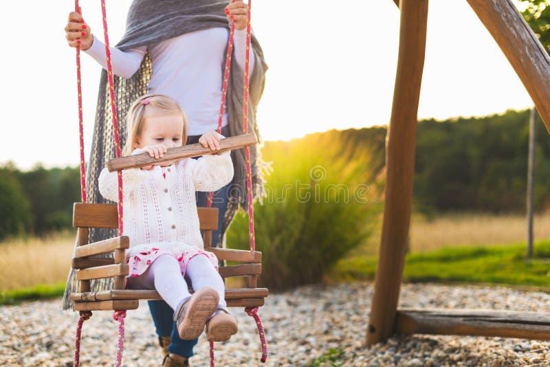 Allein erziehende Mutter mit der Kleinkindtochter, die auf einem Spielplatz schwingt Kindheit, Familie, glücklich, Sommer-Konzept stockfotografie