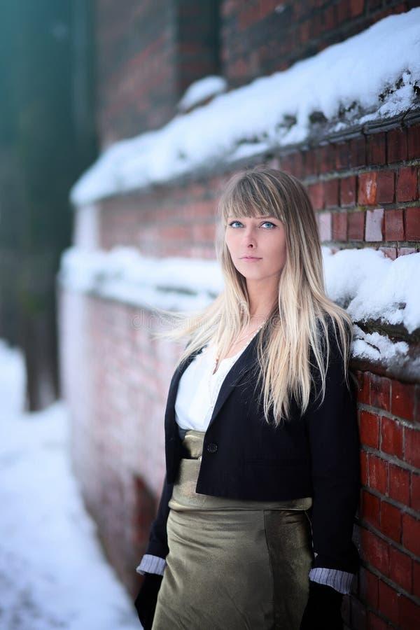 Allein junge blonde Frau im weißen Hemd und in der Jacke, die nahe der Backsteinwand bleibt stockbild