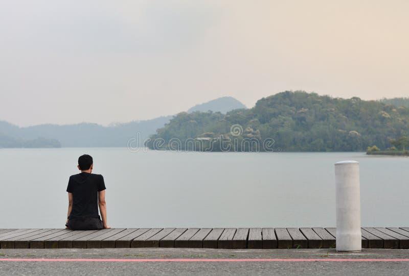 Allein junger Mann, der auf dem hölzernen Gehweg schaut zum Berg im See mit Sonnenunterganghintergrund sitzt lizenzfreies stockfoto