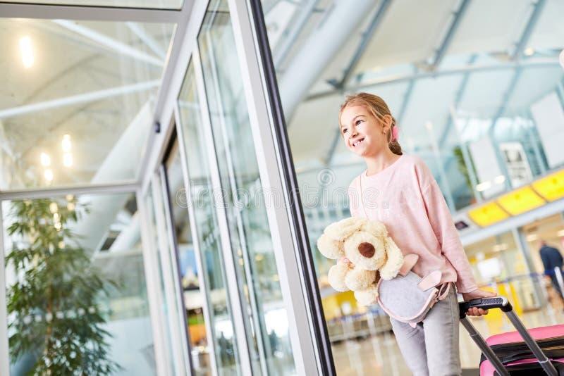 Allein reisendes Kind mit Gepäck im Flughafen stockfotografie