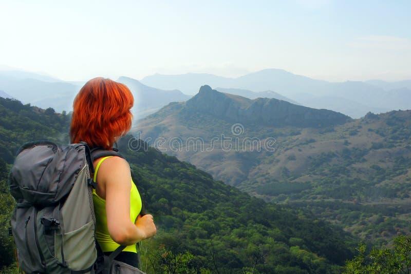 Allein stehende Frau reist in die Berge mit einem Rucksack stockbild