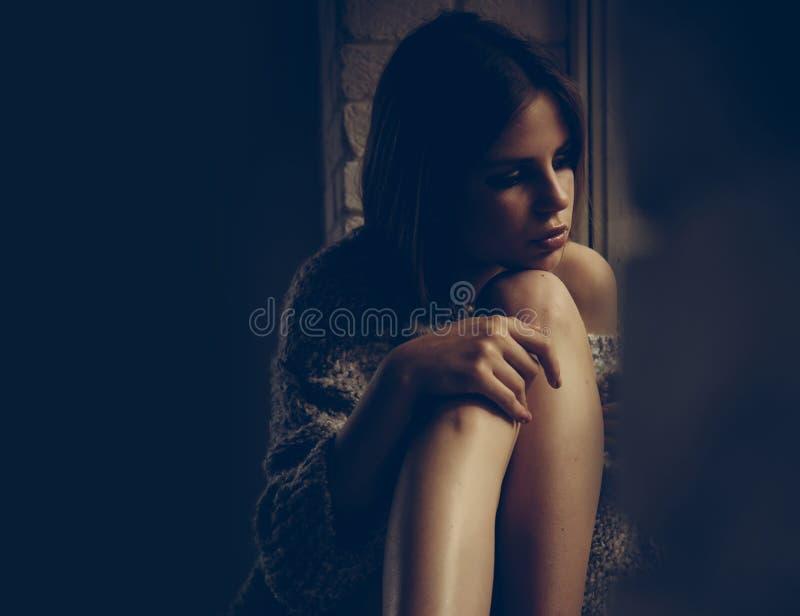 Alleine mit ihren Gedanken Frau sitzen mit den Beinen auf Fensterbrett Junge Frau mit Make-up und dem langen Haar Schönheits-Mädc stockbild