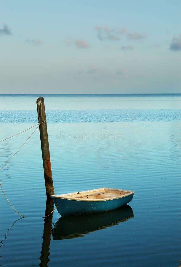 Alleines kleines Boot machte bei weichem Cyanblausonnenaufgang fest stockfotos