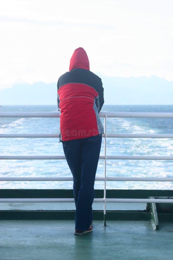 Alleinmann in der Haube, die an der Fähre steht und das Meer betrachtet stockfotografie