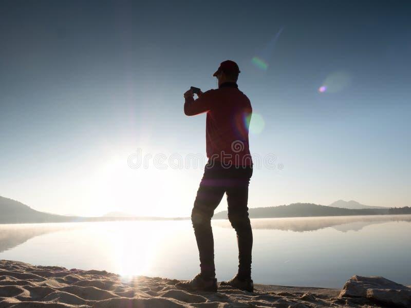 Alleinmann an der Küste unter Verwendung des Handys, zum von selfie Foto mit dem Meer hinter ihn zu machen lizenzfreie stockfotografie