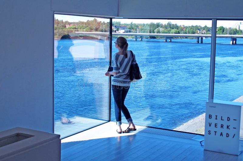 Alleinstehende Frau am Museum, das heraus Fluss und Teilen der Stadt betrachtet stockfotos