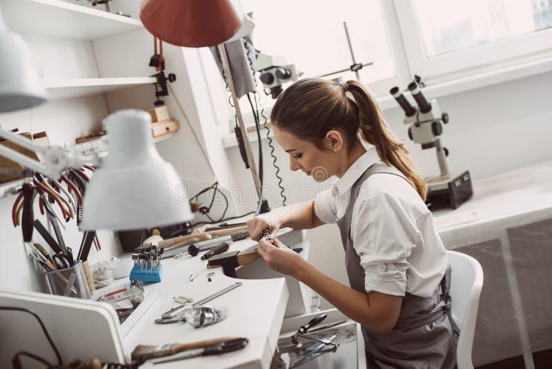 Allen over het werk Sluit omhoog portret van een vrouwelijke juwelier werkend aan een ring bij haar werkbank Juwelen makend proce royalty-vrije stock foto's