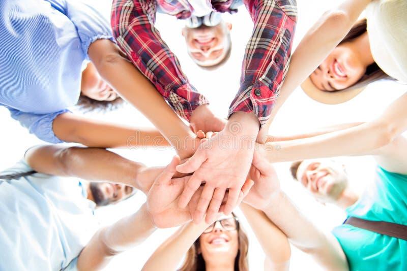 Allen samen! Lage hoekmening van gelukkige studenten die hun han zetten royalty-vrije stock afbeelding