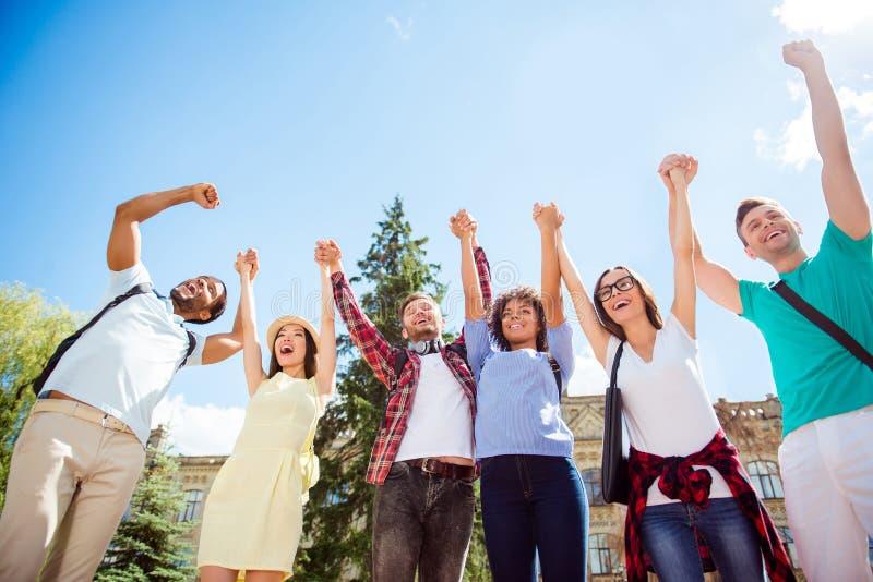 Allen samen! Lage hoekmening van gelukkige studenten met opgeheven wapens stock afbeeldingen