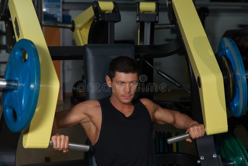 Allenamento abbronzato dell'atleta sulla macchina di esercizio fotografie stock libere da diritti