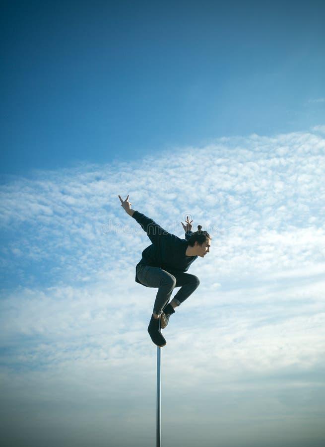 Allenamento del ballerino dell'uomo forte sul palo Dancing del giovane sul pilone mosca macho dell'uomo sul fondo del cielo blu B immagini stock